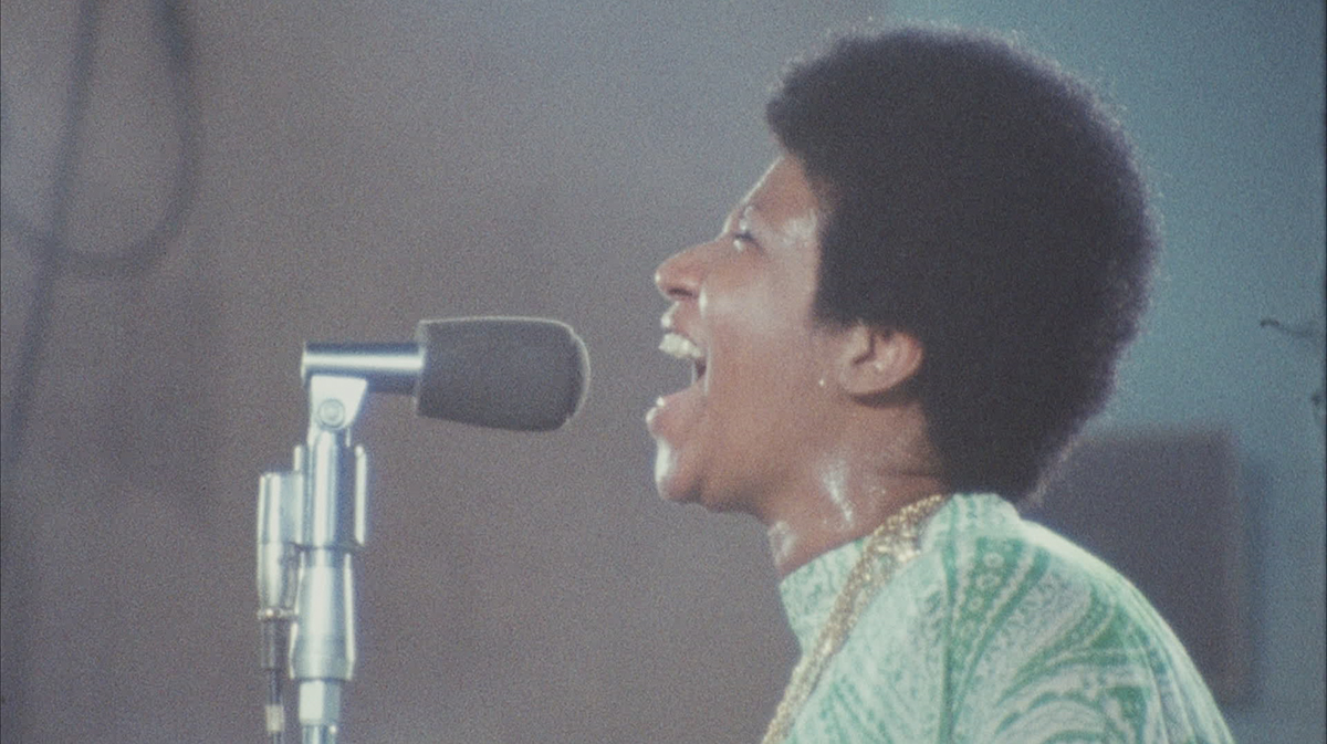 A young Aretha Franklin, sweating and wearing a green dress, sings passionately into a microphone.