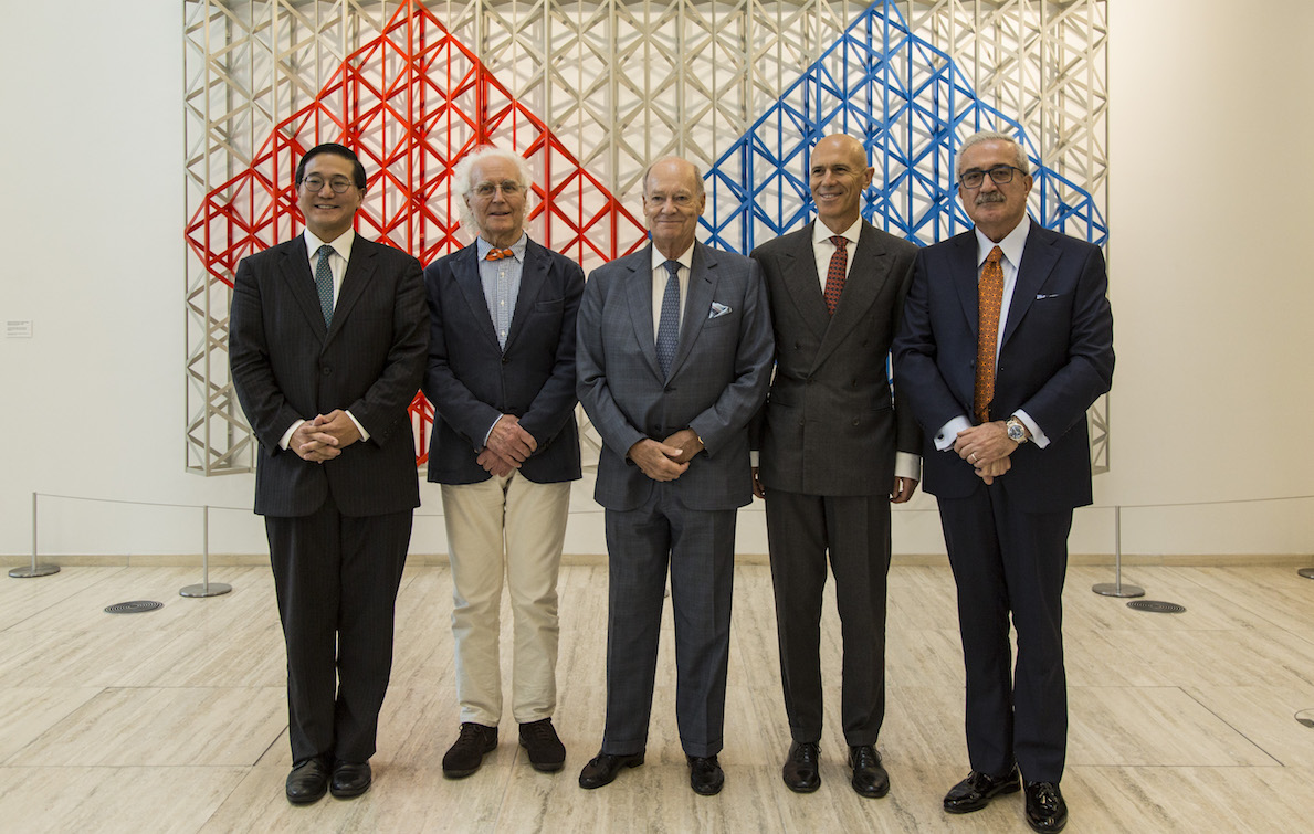 6 older men dressed in suits standing in front of an art piece