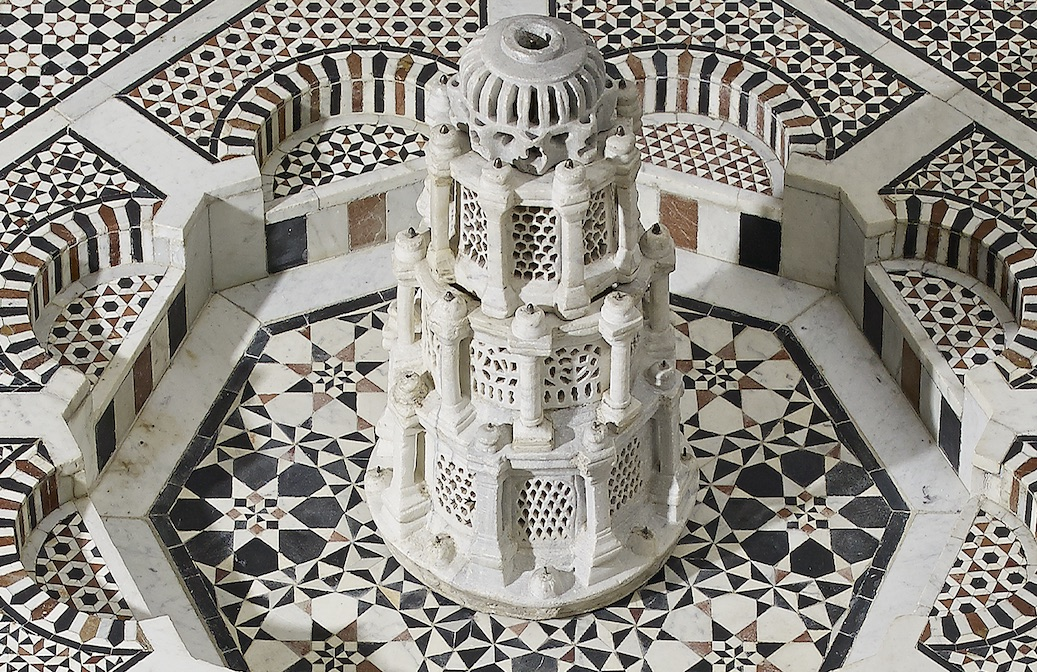 An ornately tiled base with a minaret-like fountain at the centre.