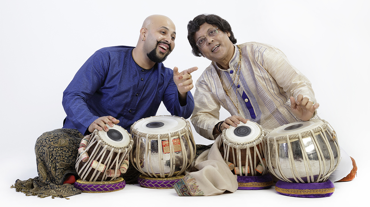 A bald Indian man in a blue shirt leans towards an older man. Both rest their hands on tablas, a type of South Asian drum