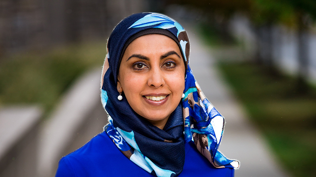 Canadian filmmaker and writer, Zarqa Nawaz, wearing a blue scarf and smiling in the foreground of a park
