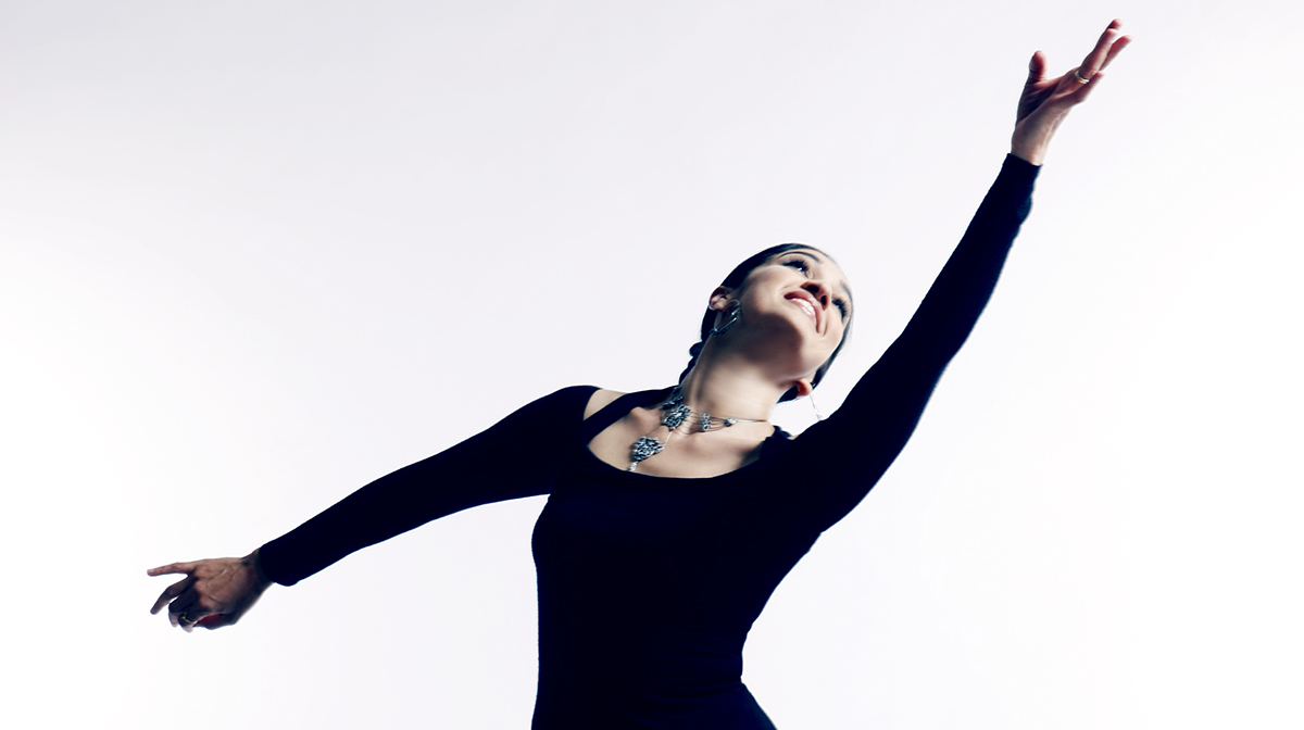A female dancer in black clothes smiles and stretches her hand towards the sky
