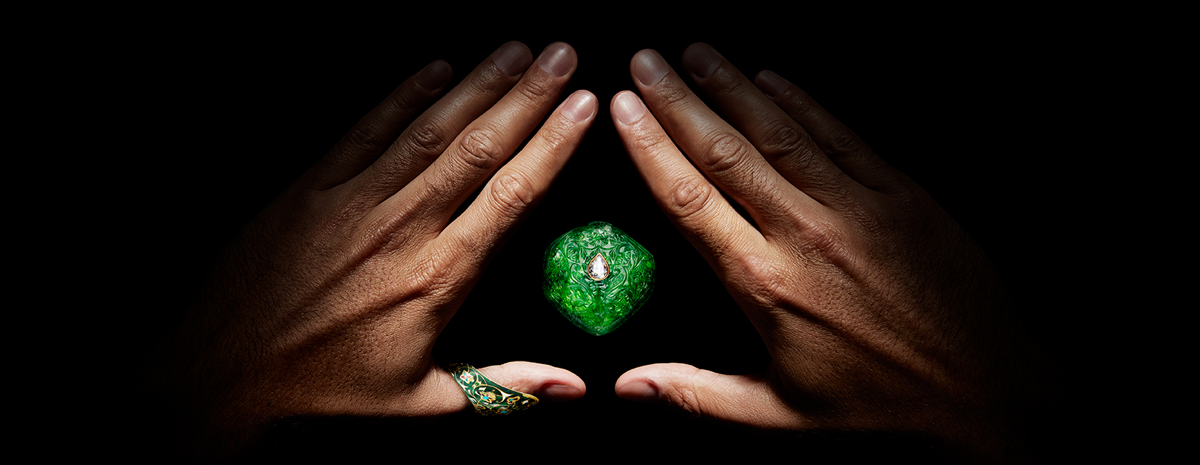 Two hands, with the fingers and thumbs pressed together to form a diamond shape, framing a bright green, engraved jade pendant.