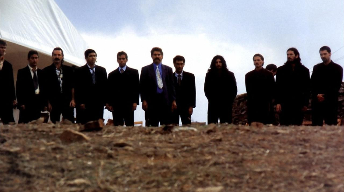 Eleven men in dark suits stand in a line and stare ahead at a pile of dirt