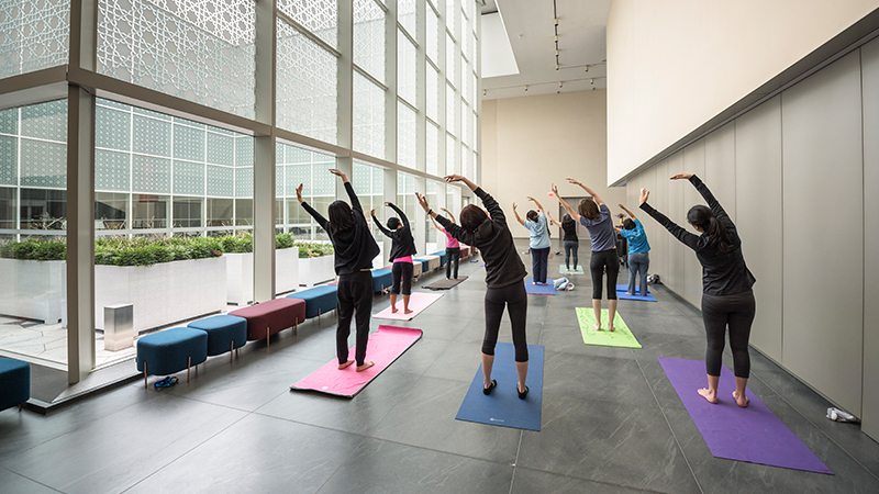 A group of women, facing away, lean to the left with arms raised, during a yoga class in the Museum's atrium.