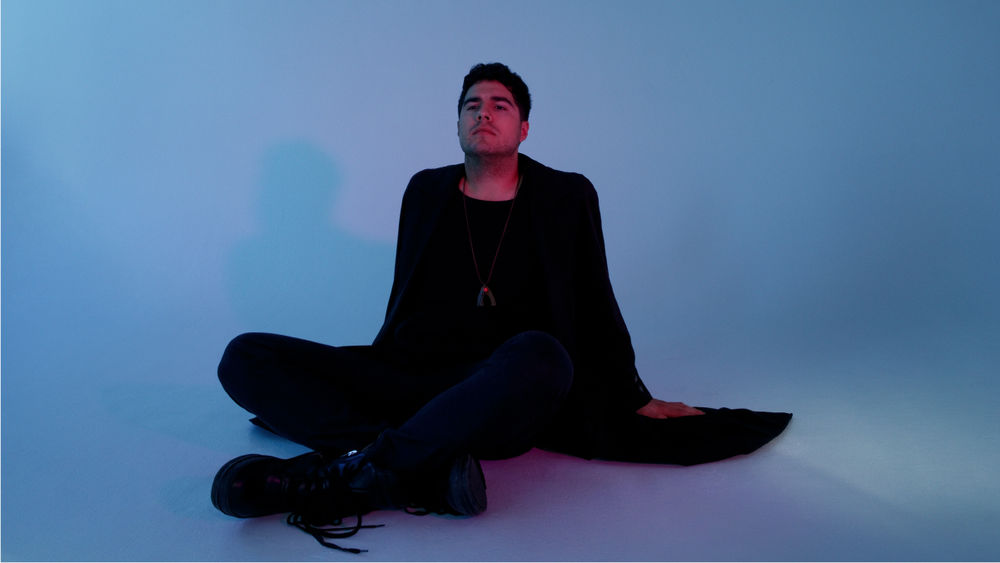 Against a blue backdrop and floor, Jeremy Dutcher sit cross-legged and leans back on his arms, looking upwards.