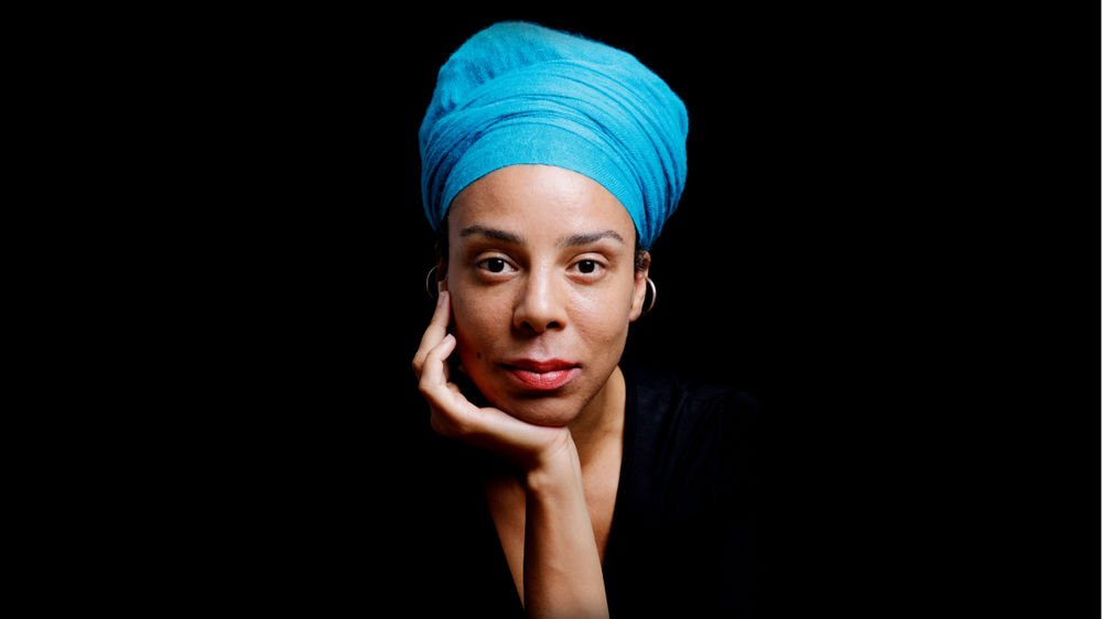 Tanya Evanson, wearing a blue turban, poses with her chin on her hand, against a black backdrop.