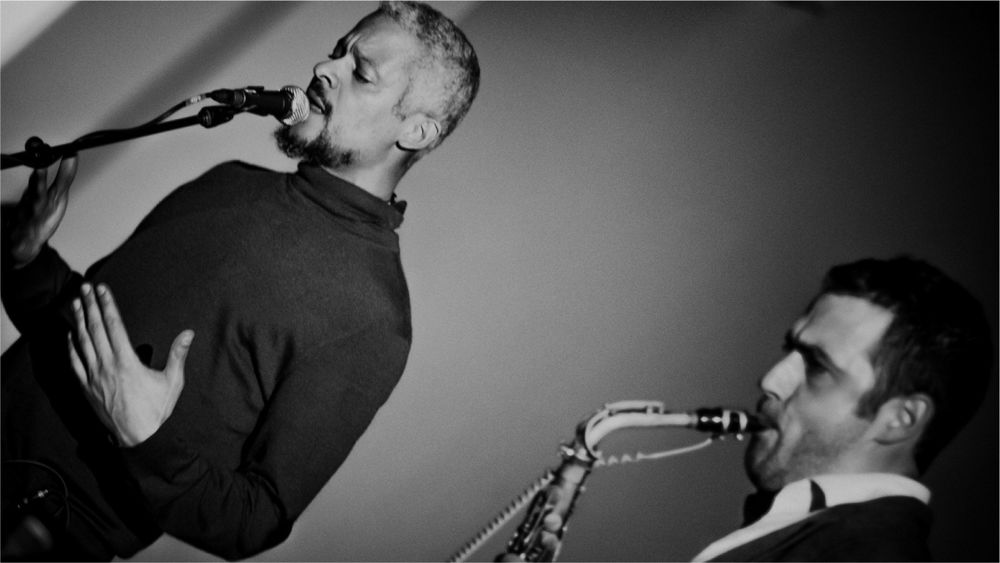 A black and white image of Kaie Kellough singing into a mic and Jason Sharp playing sax.