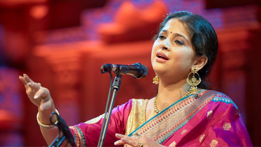 Kaushiki Chakraborty, wearing a magenta and gold shalwar kameez, sings on stage in front of a microphone against a red backdrop.