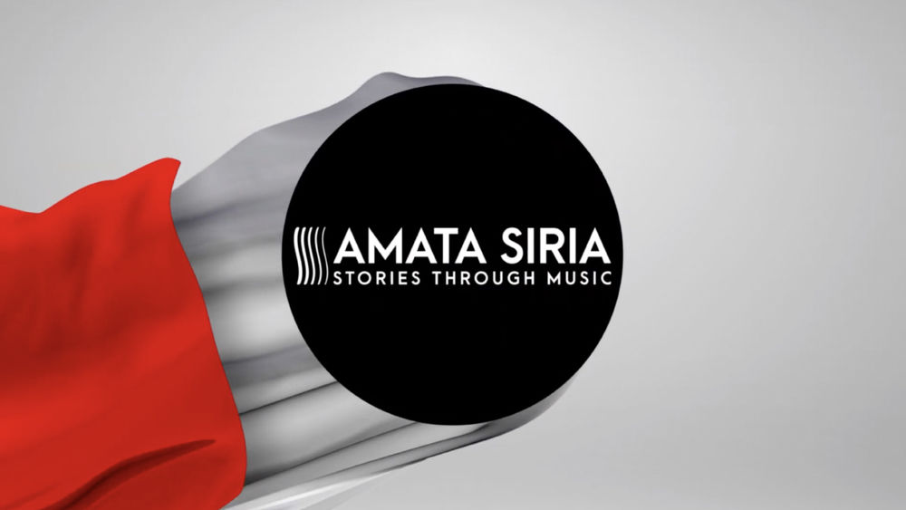 "A black circle with the words ""Amata Siria Stories Through Music"" in white, all against a grey and red backdrop."