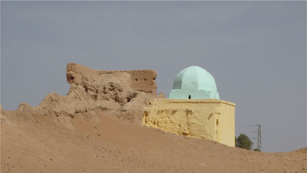 A pale green dome sits atop partly ruined walls emerging from sand dunes.