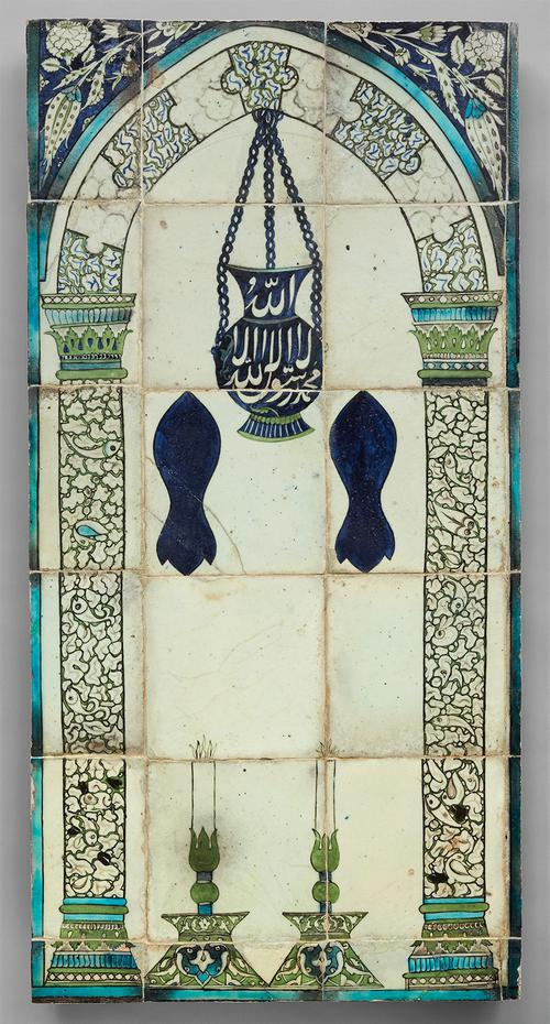 A panel of 18 tiles showing an arch supported by decorated green, blue, and white columns. Between them are two large candlesticks. A blue lamp with a white inscription hangs from the top, and two dark blue footprints float below. Outside the arch are flower motifs on a blue background.