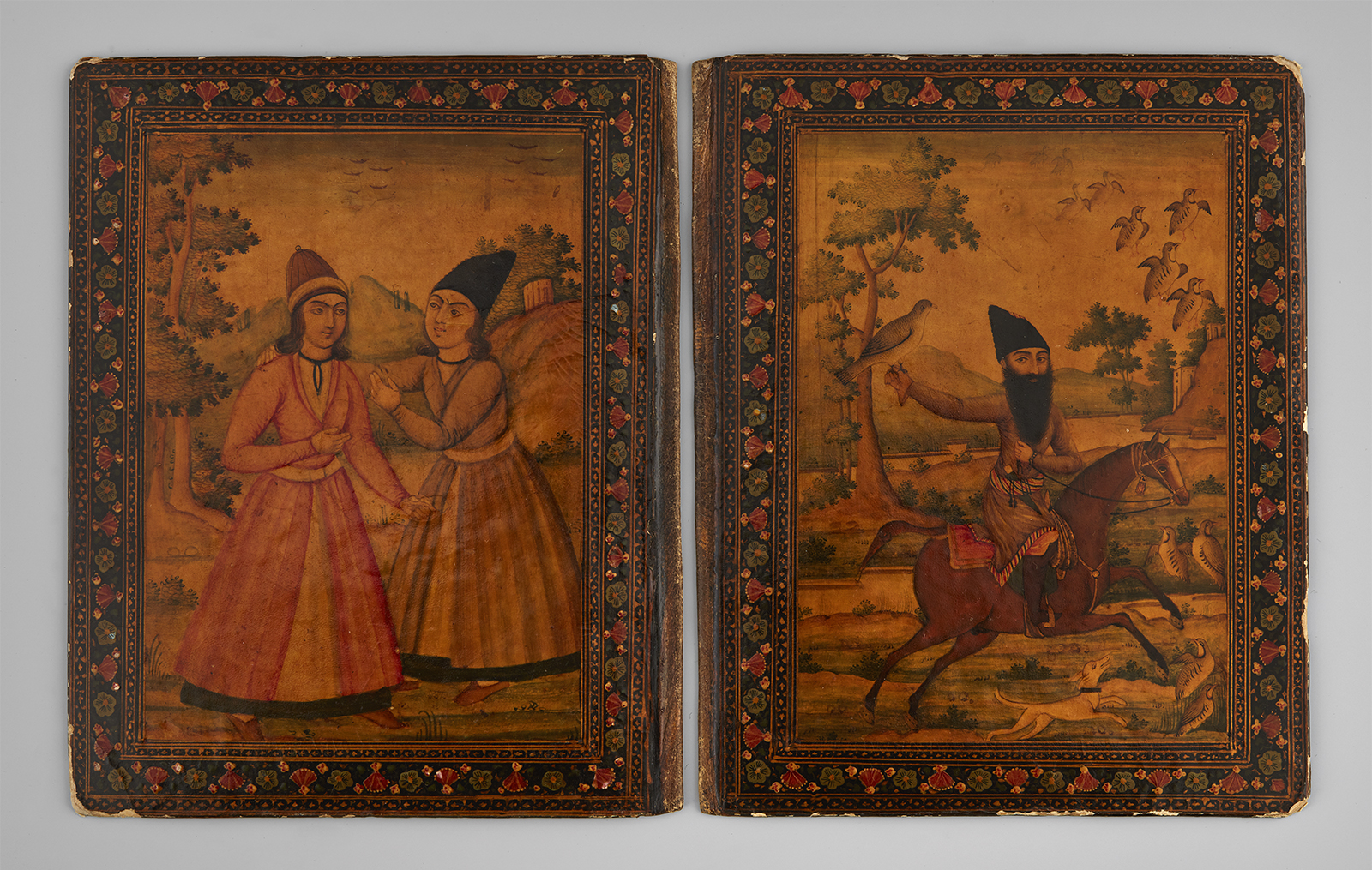 A pair of lacquer book covers from 19th-century Iran, with one panel showing a youth, possibly young prince, talking with a young travelling dervish, while the other panel shows a bearded dervish riding a horse.