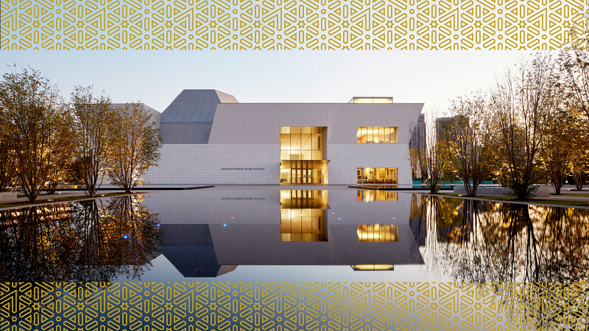 The Aga Khan Museum at dusk, seen from a distance, so that the building's upside-down reflection is also visible in the Museum's central Reflecting Pool.