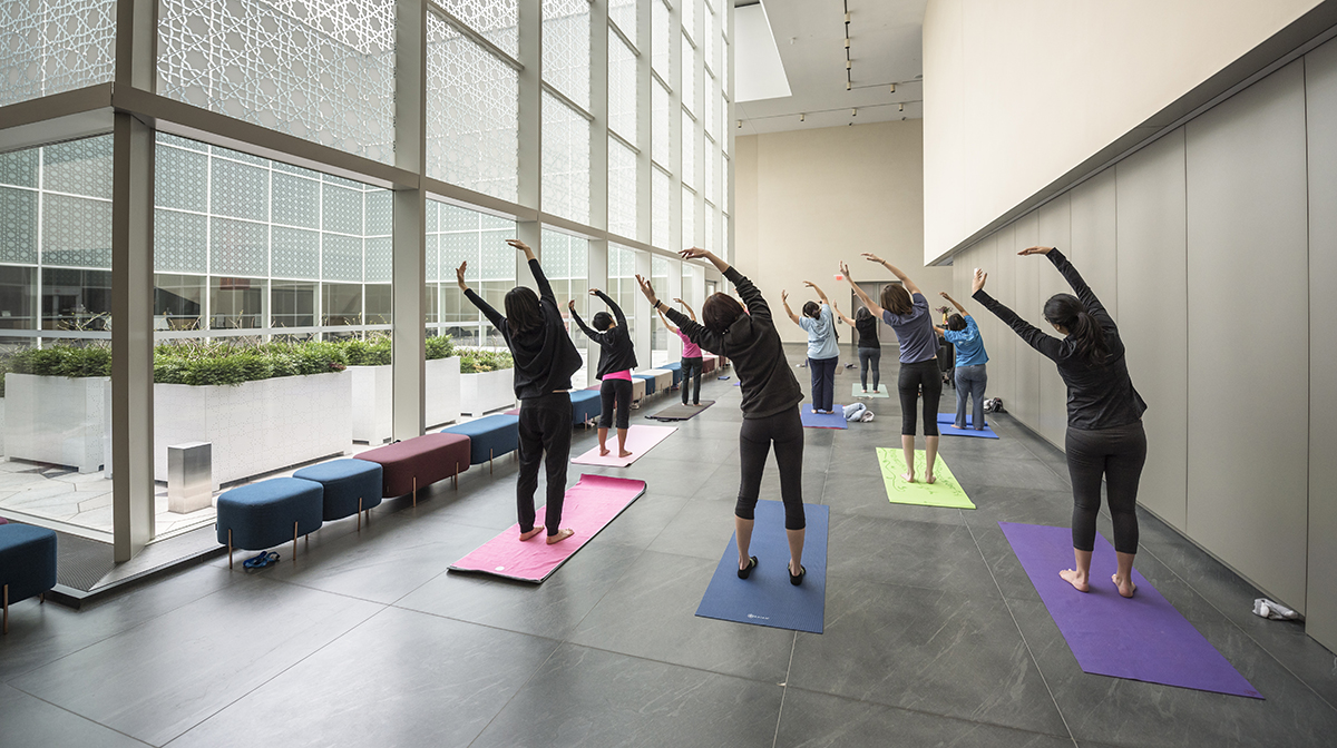A group of yoga students in a standing yoga pose in the Museum atrium,