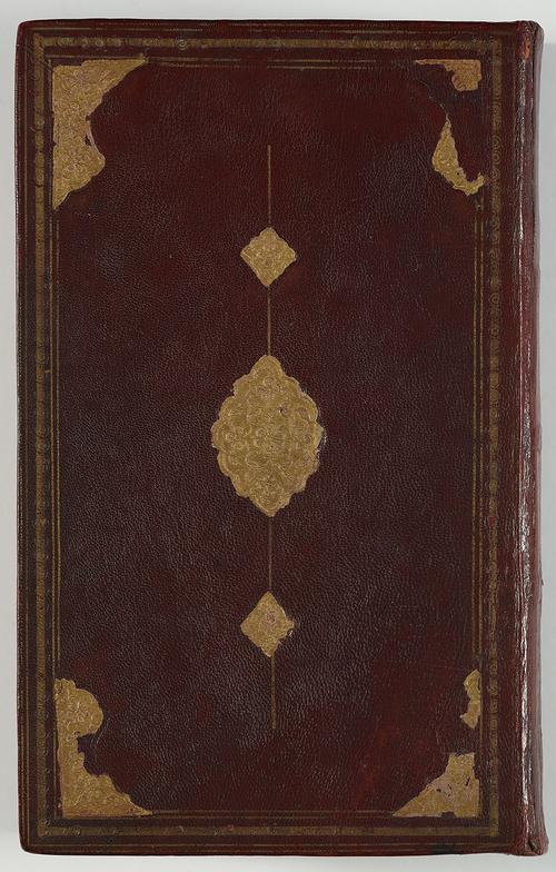 View of the front of a book bound in dark brown leather. There is a border of gold-embossed tooling, with large corner shapes and a central medallion with small pendants. The gold foil is falling off and not complete.