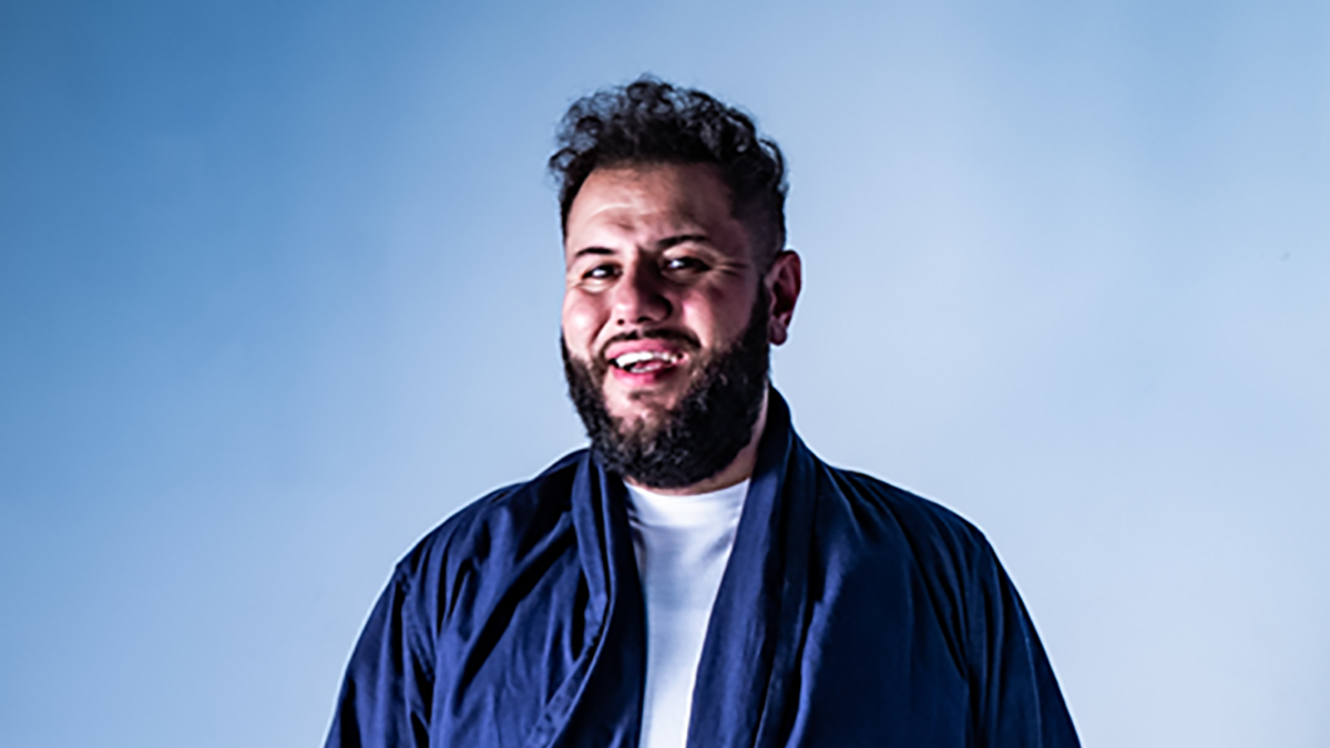 Comedian Mo Amer laughs in front of a blue backdrop.