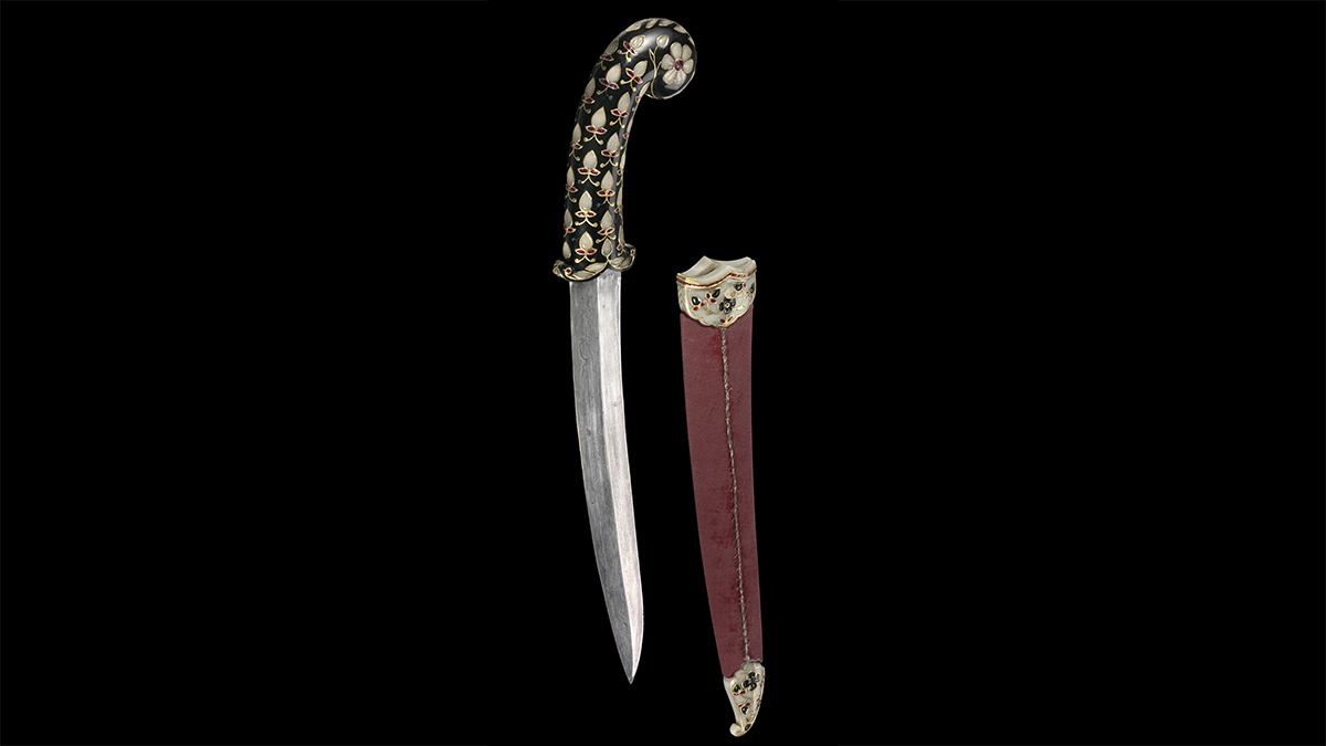 Steel dagger with a ruby-studded jade hilt beside its wooden scabbard, which is set with jade, gold, and rubies.
