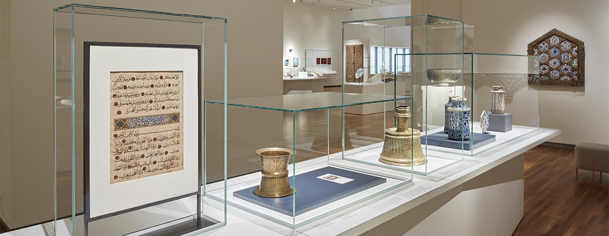 Museum collection gallery, featuring multiple objects on a large rectangular showcase under four glass top covers.