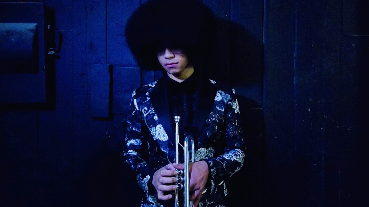 William Franklyn Leathers, wearing a floral suit jacket, holds his trumpet in a dark blue room.