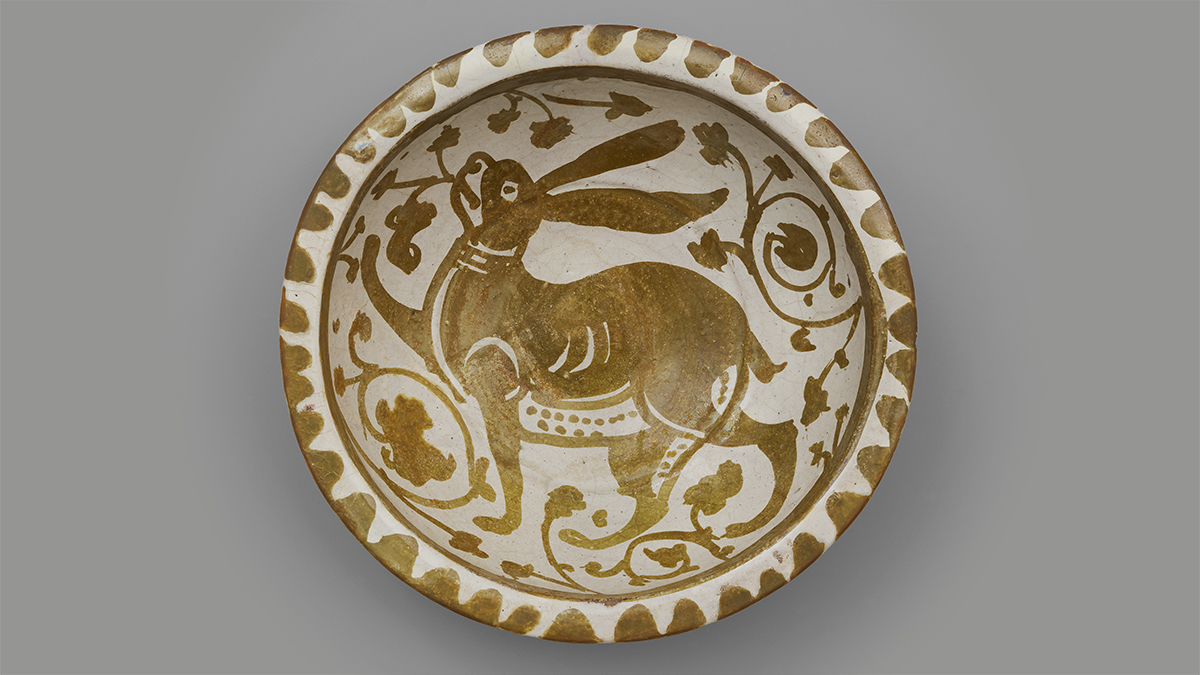 A ceramic bowl with a golden lustrous sheen, and a jovial long-eared hare painted at the centre.