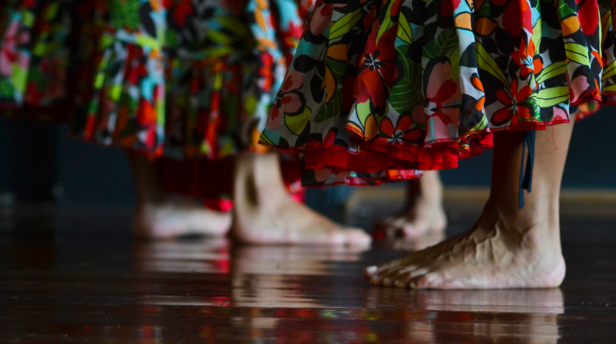 A close up of two dancers bare feet and their red flower-patterned skirts.