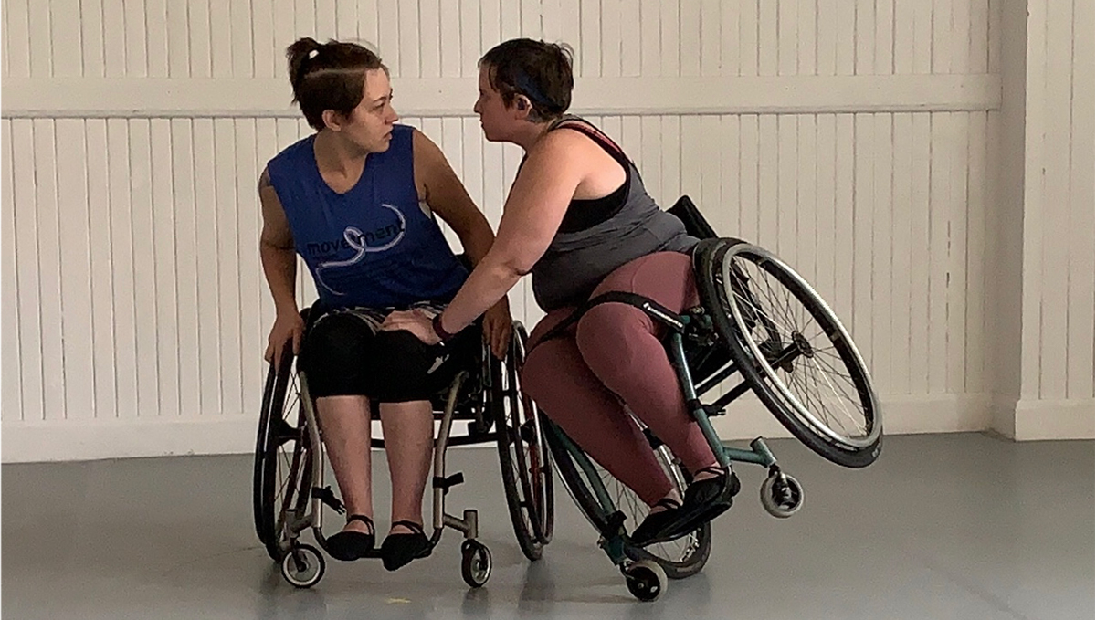 Dancer Jenna Roy sits in a wheelchair as dancer Shay Elrich tips herself in a wheelchair onto Roy.