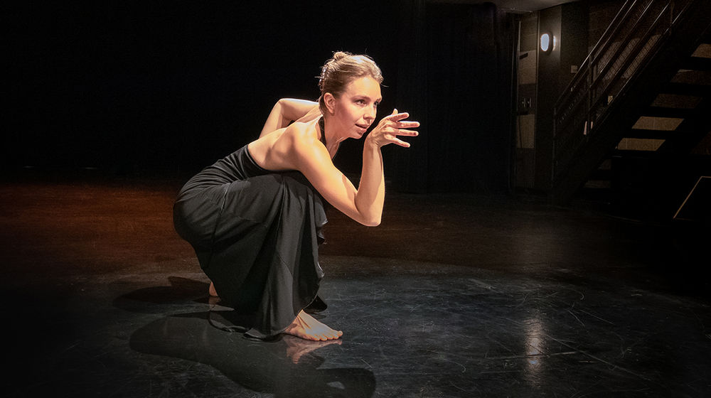Anaya Bobst, wearing a black dress, crouches barefoot in a dance pose on a dark stage.