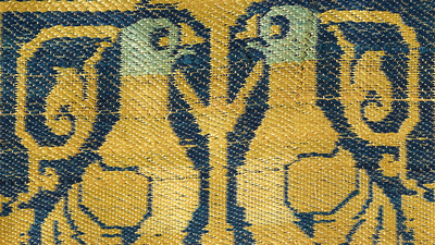 Two golden yellow embroidered birds face each other against a blue silk background.