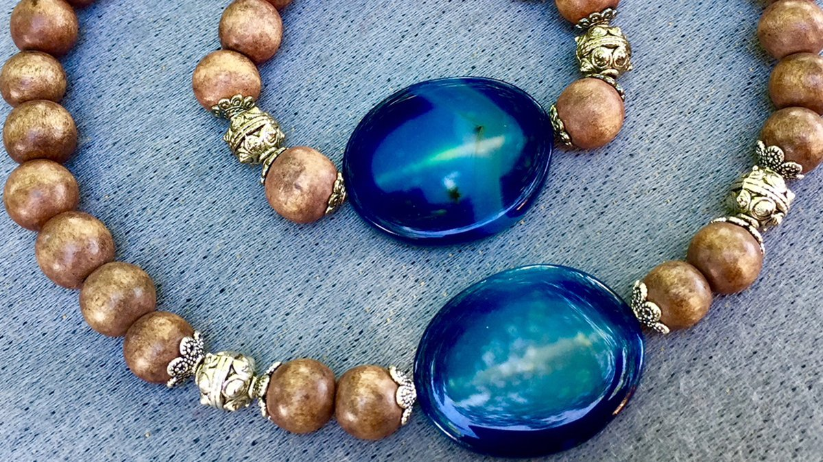 A beaded wooden bracelet with silver brackets and a large blue gem rests inside a matching necklace.