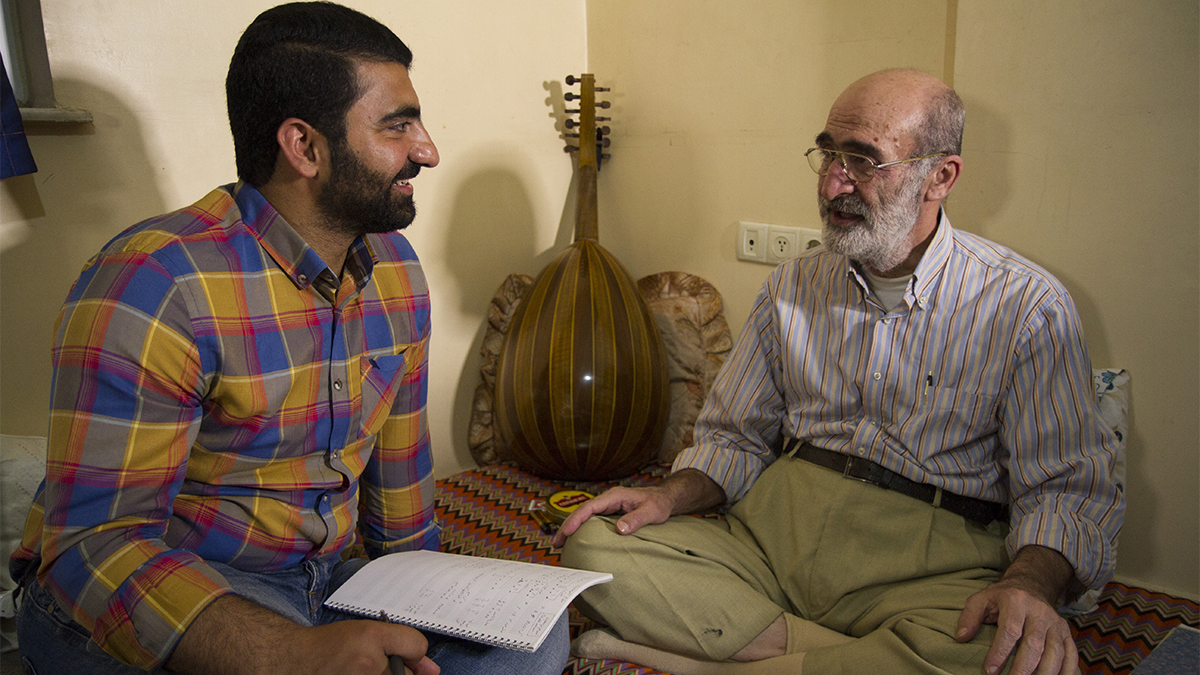 A young man and an older man sit talking, while an oud leans against the wall.