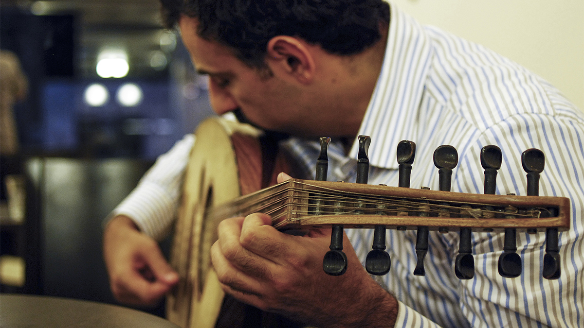 A man wearing a collared shirt plays the oud.