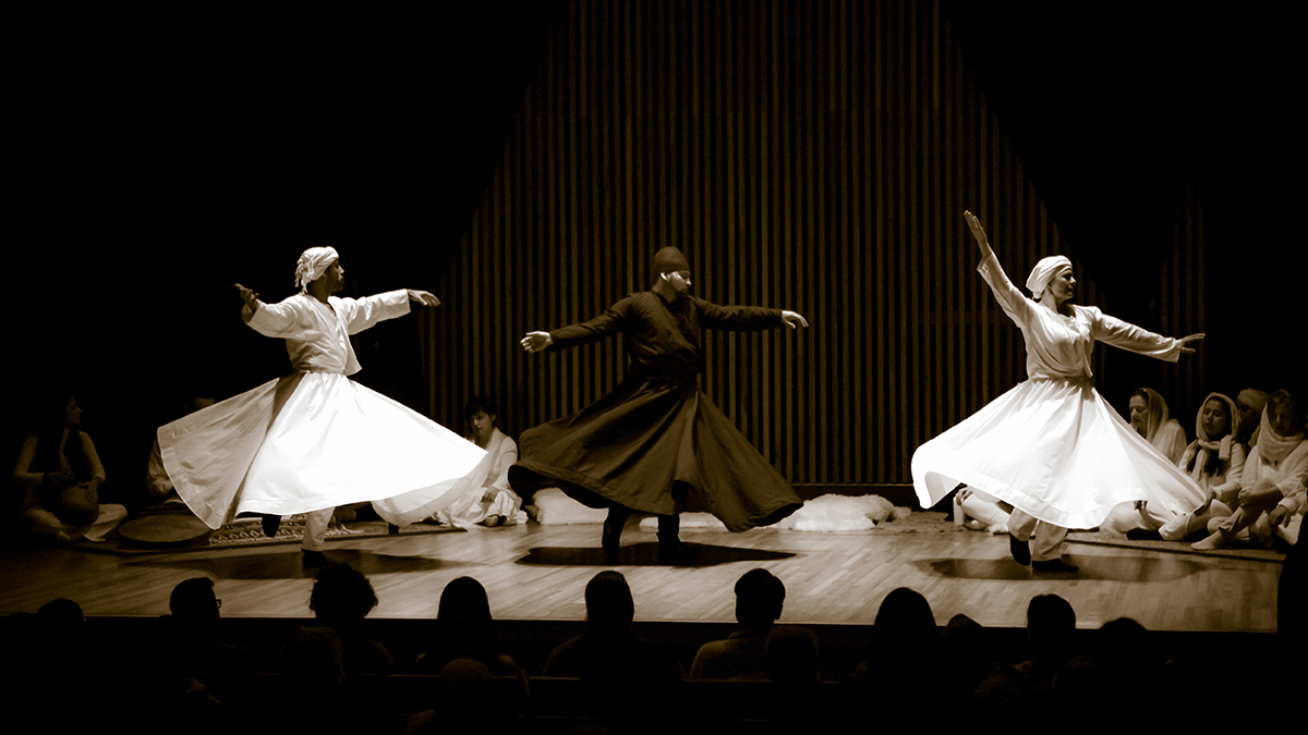 Three whirling dervishes twirl on a stage surrounded by seated onlookers.