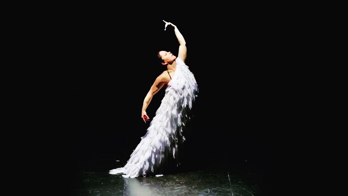 Carmen Romero, wearing a purple feathered dress, strikes a flamenco pose on a dark stage.