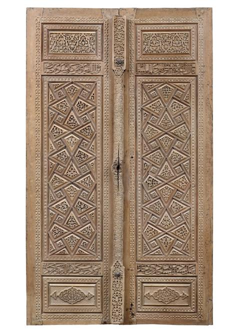 Brown wood doors, each rectangular form, the central tall vertical panel flanked above and below by smaller panels, one door with central door post to cover the join. Featuring geometric interlace design of strapwork, the polygons thus formed slightly raised and deeply carved with floral designs.