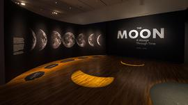 "An exhibition space with ""The Moon"" written on a black wall and images of the moon on the wall."