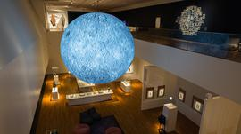 An exhibition space with a lit up moon sculpture hung from the ceiling.