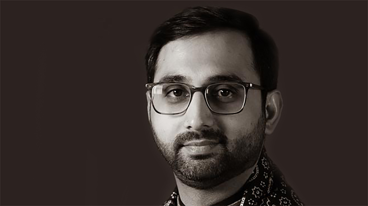 A black and white portrait of Umair Jaffar, wearing glasses and a patterned shirt.