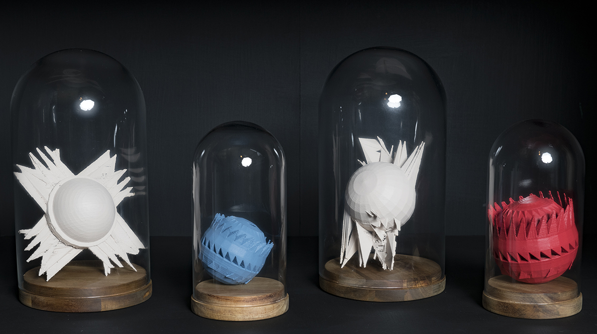 Four exoplanet models in white, blue, and red housed in bell jars.