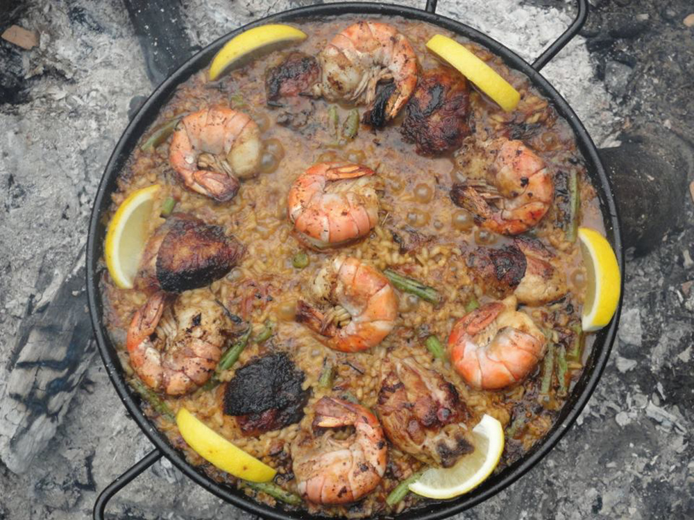 Paella cooking in a metal pan over an open fire.