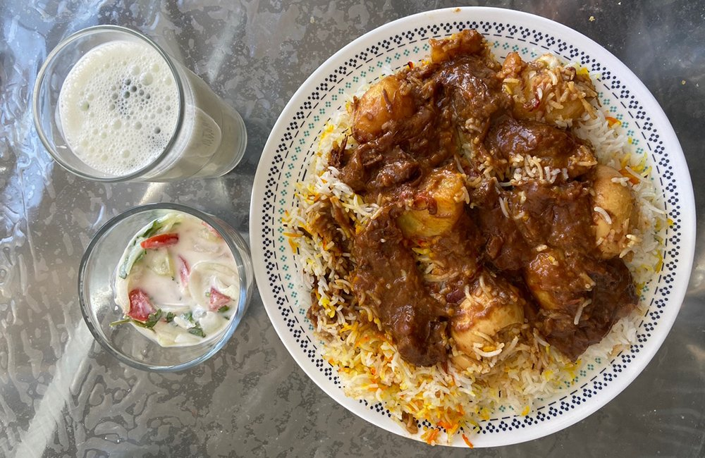 A dish of chicken biryani sits on a table along with two glasses containing a milky sauce or beverage.