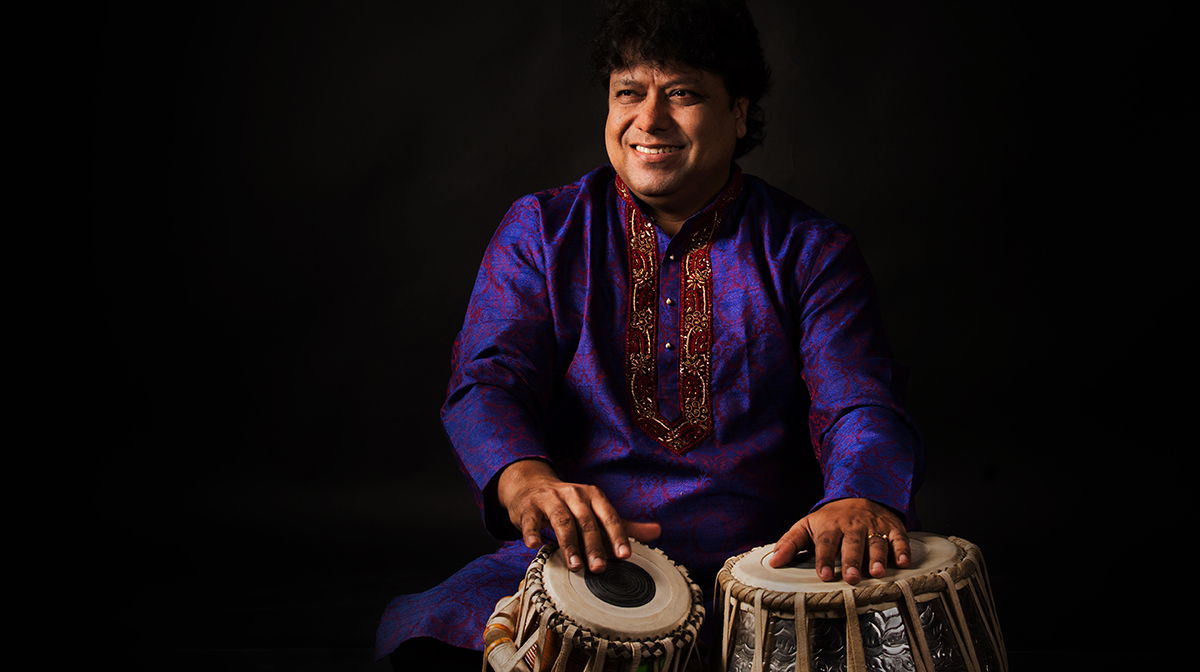 Pandit Subhankar Banerjee sits with his hands on the tabla, smiling widely