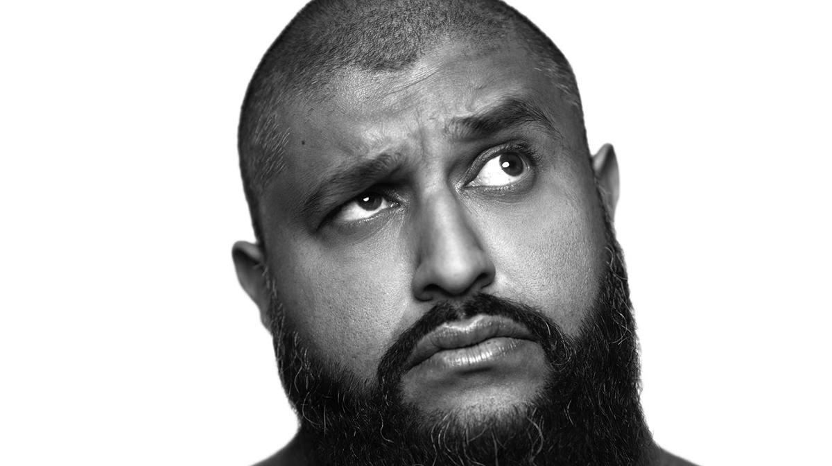 Black and white portrait of comedian Azhar Usman raising one eyebrow