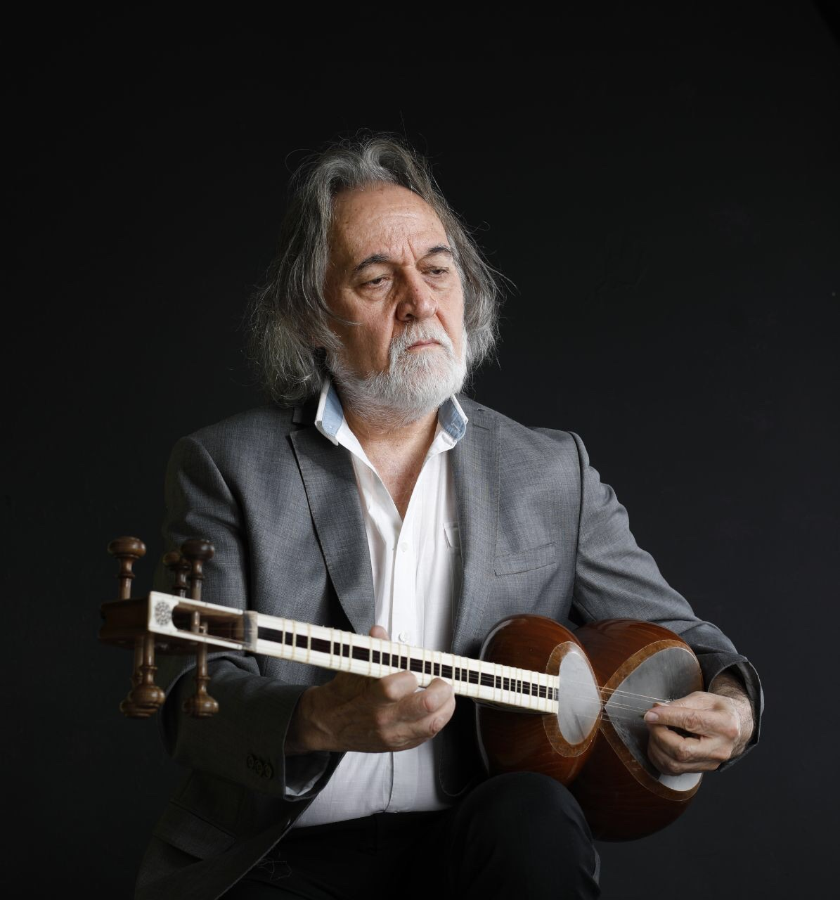 A portrait of Majid Derakshani holding an Iranian string instrument known as the tar