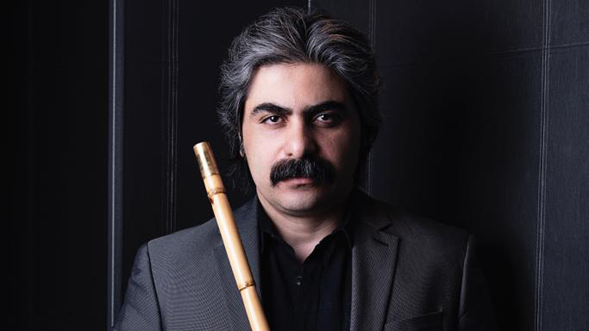 A portrait of Shaho Andalibi holding an Iranian flute known as the ney