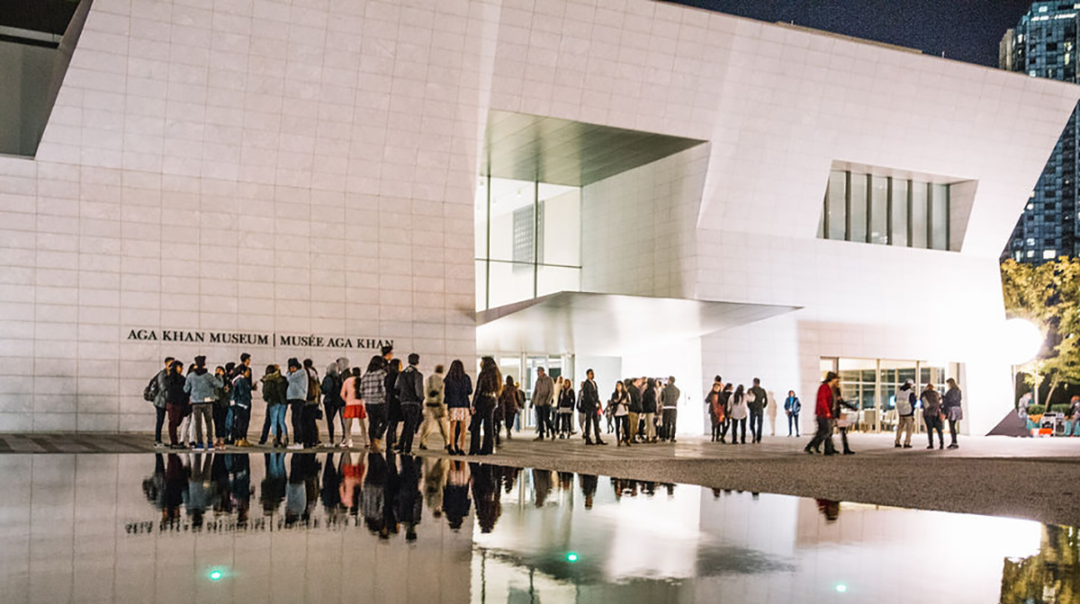 A crowd stands outside the Museum near the reflecting pool at night.