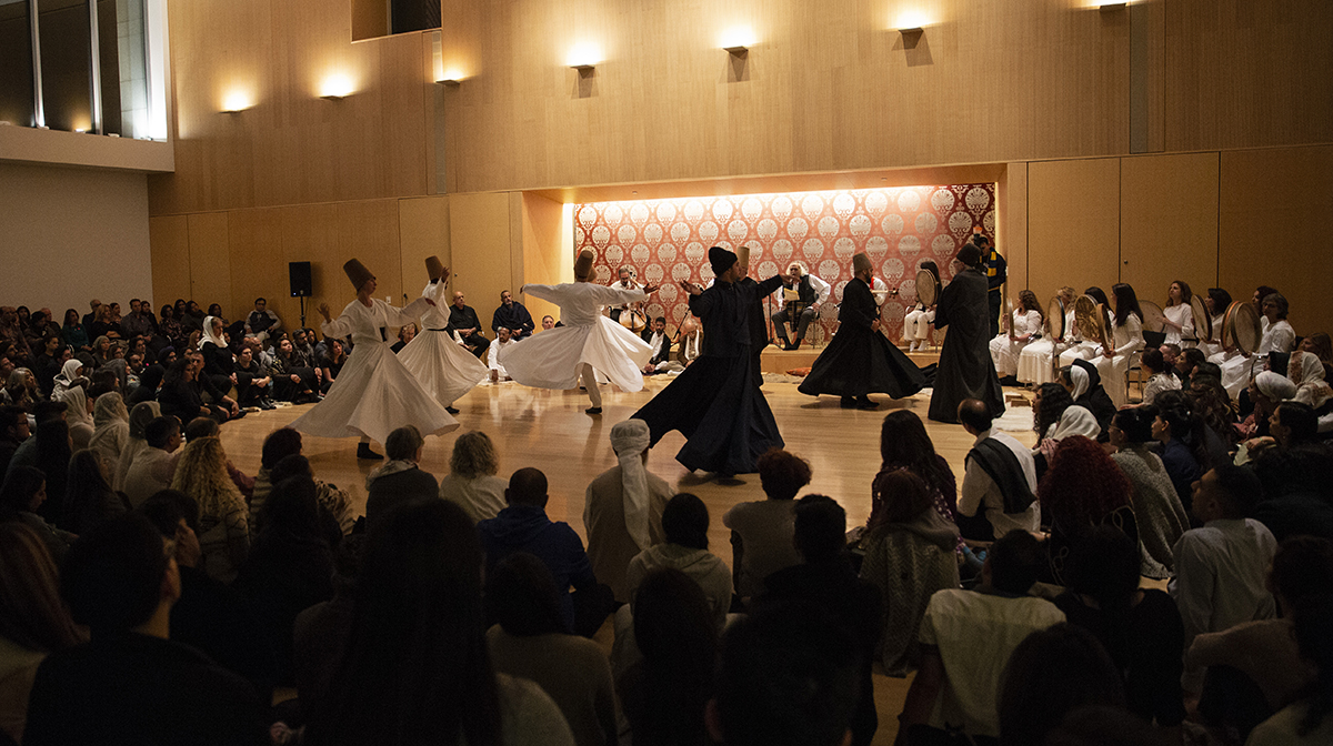 Whirling dervishes twirl onstage amidst a crowd of onlookers in the Ismaili Centre, Toronto