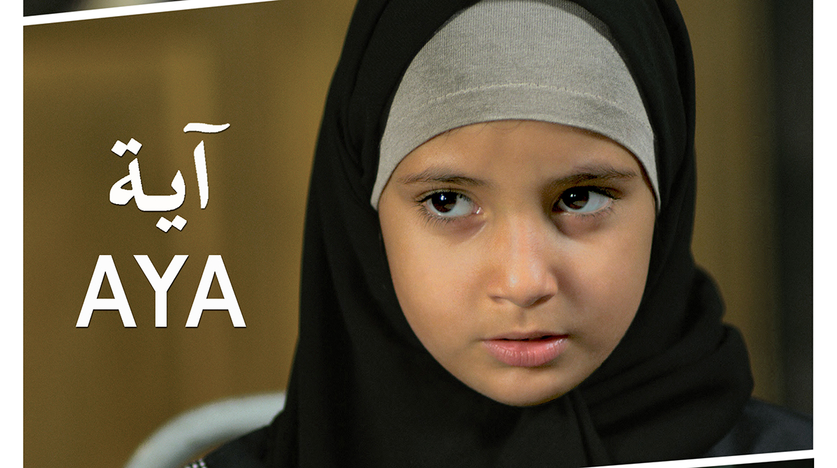 A serious little girl wearing a hijab.
