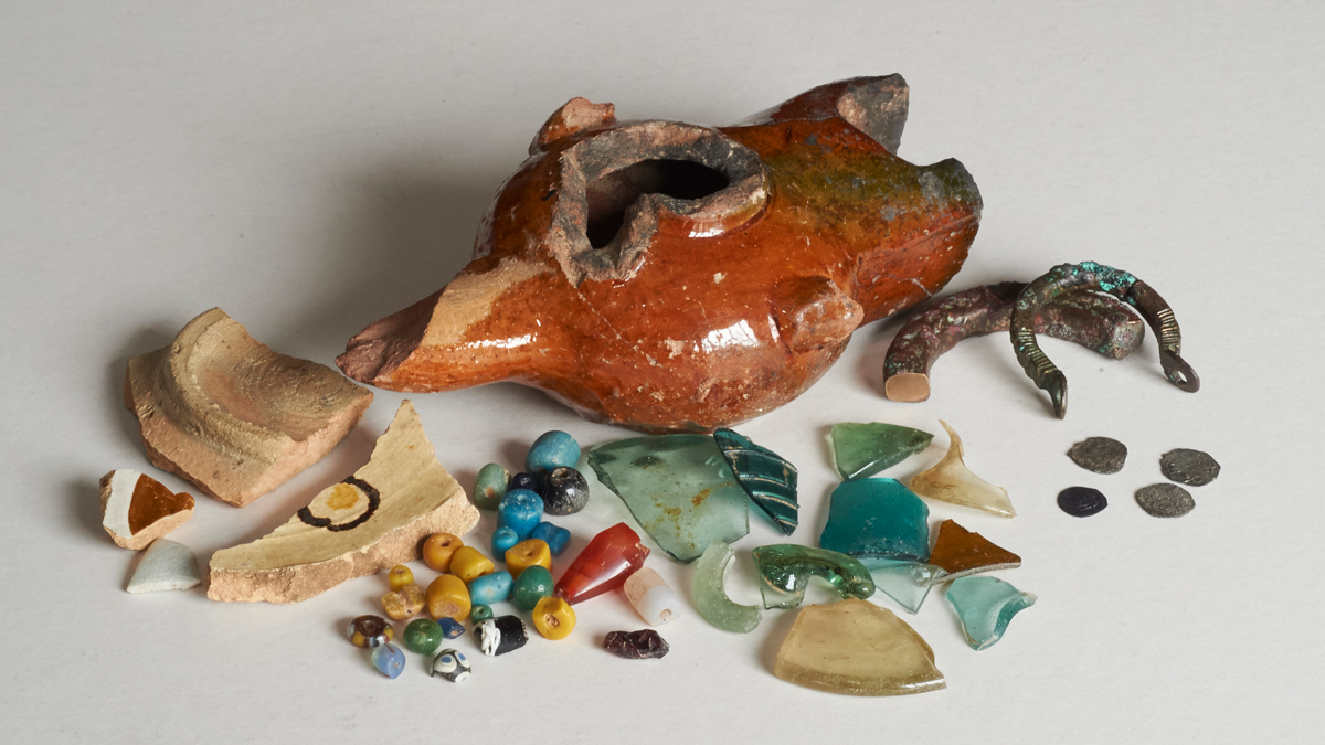 An array of fragments made of glass, ceramics, beads, coins, and metal against a grey backdrop.
