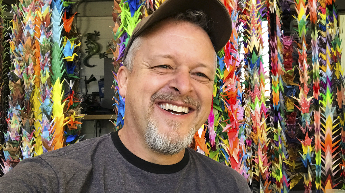 Rick Allred wearing a cap smiles with colourful origami cranes in the background.